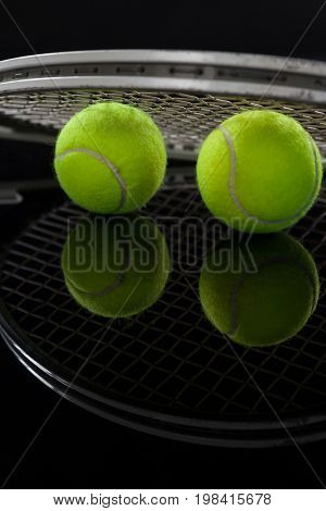 Close up of fluorescent yellow tennis balls with racket with reflection against black background