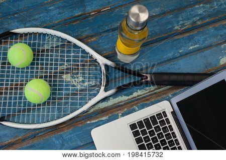 High angle view of laptop by tennis racket and balls with water bottle on blue wooden table