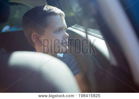 Thoughtful teenage boy sitting in the back seat of car