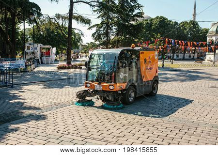 Editorial image of street janitor using cleaning machine to sweep and clean sidewalk tile in Istanbul, Turkey on June 15, 2017.