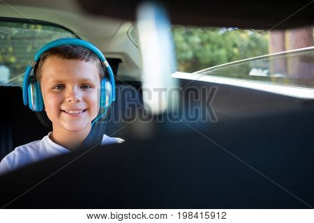 Portrait of smiling teenage boy with headphones sitting in the back seat of car