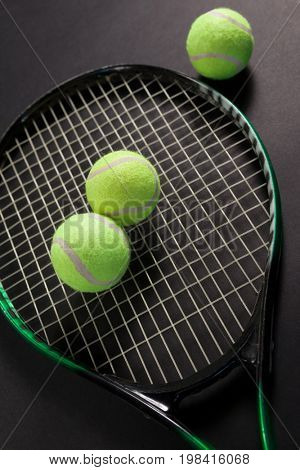 High angle view of fluorescent yellow tennis balls and racket against black background