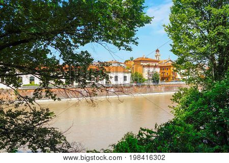 Verona, Italy - July, 10, 2017: embankment of Adige river in Verona, Italy, veiw from a frame made with tree brenches