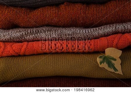 Close-up of woolen stack with autumn leaves