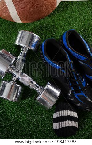 High angle view of dumbbells by sports shoe and American football on field