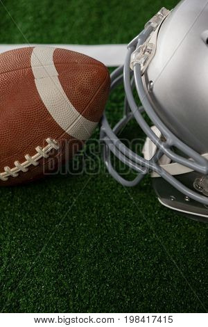 High angle view of American football by sports helmet on field
