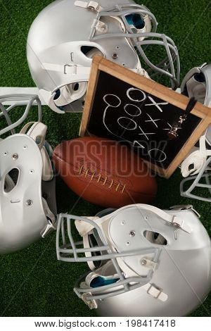 Overhead view of American football amidst sports helmet on field