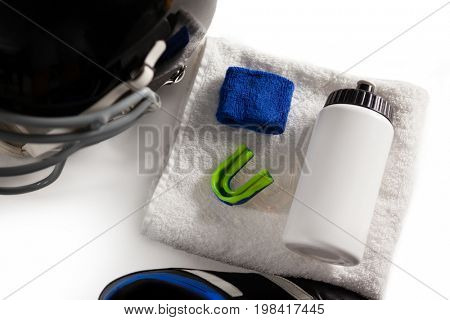High angle view of wristband and bottle on napkin by sports helmet