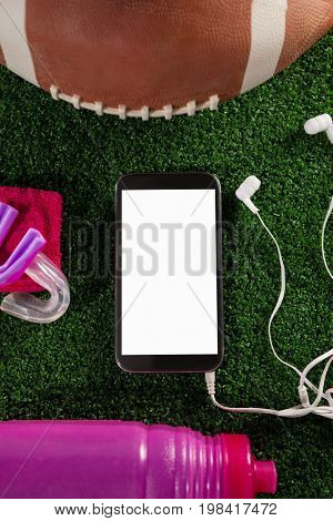 Overhead view of smart phone by American football on football