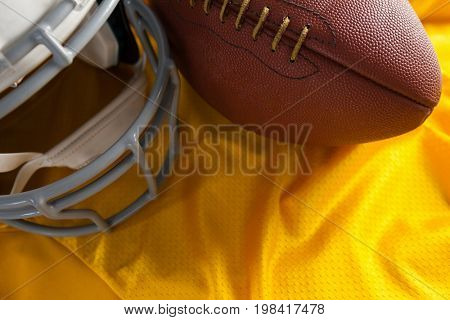 Close up of American football and helmet on yellow jersey