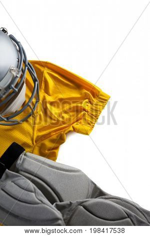 Directly above shot of sports jersey with helmet on white background