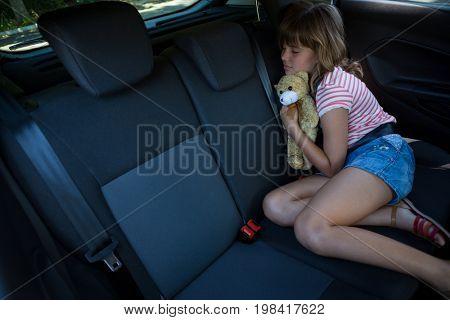Cute teenage girl sleeping in the back seat of car