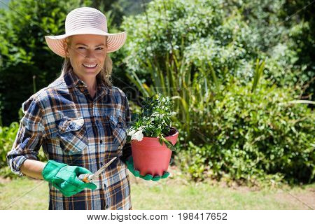 Portrait of happy woman holding sapling and trowel in garden on a sunny day