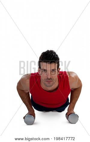 Portrait of determined sportsperson exercising with dumbbells against white background