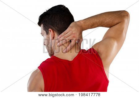 Rear view of American football player suffering from neck pain while standing against white background
