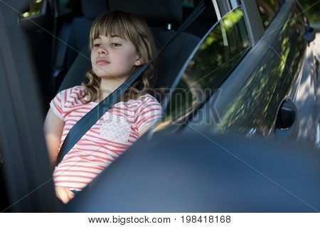 Thoughtful teenage girl sitting in the back seat of car