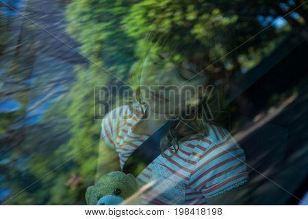 Cute teenage girl with teddy bear sleeping in the back seat of car