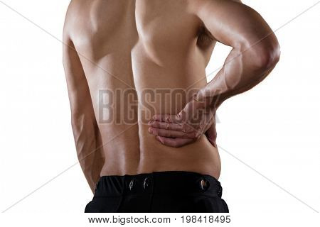 Midsection of shirtless sportsperson suffering from pain while standing against white background