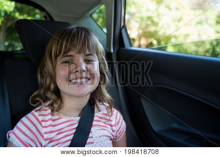 Portrait of happy teenage girl sitting in the back seat of car