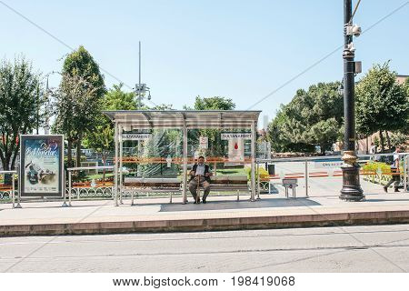 Editorial image of lonely elderly man sitiing on a bench at Sultanahmet bus station waiting for transportation, Istanbul, Turkey on June 15, 2017.