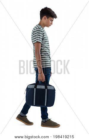 Teenage boy walking with bag against white background