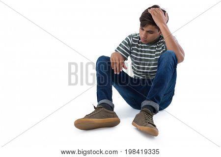 Sad teenage boy relaxing against white background