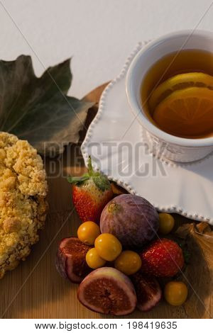 Overhead of various fruits, autumn leaves and cup of green tea on chopping board
