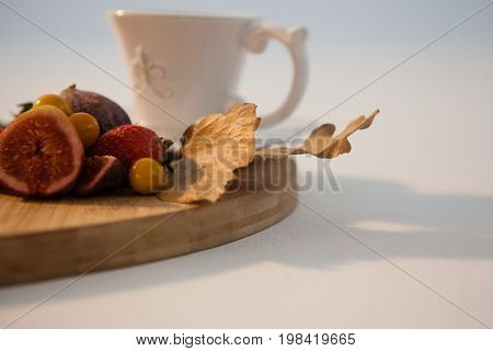 Autumn leaves, various fruits and cup of tea on chopping board against white background