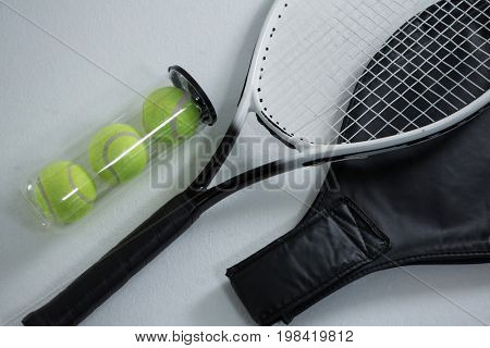 High angle view of tennis racket by balls in container on white background