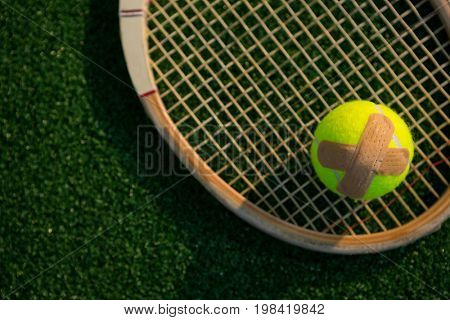 Overhead view of tennis ball with bandage on racket at field