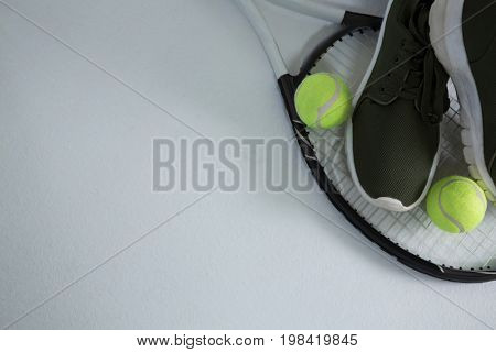 Cropped image of sports shoe with balls on racket over white background