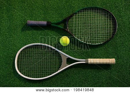 Overhead view of rackets with tennis ball on playing field