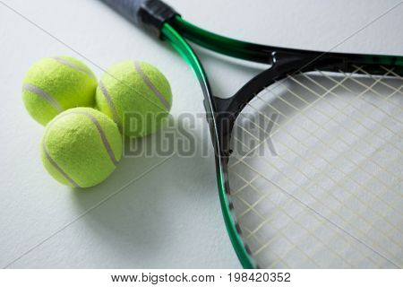 High angle view of tennis balls with racket on white background