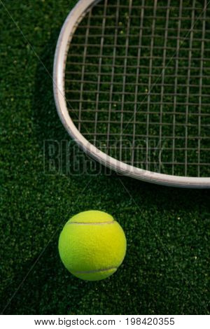 Cropped image of racket by tennis ball on playing field