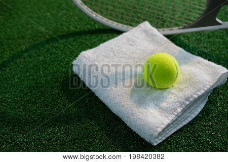 Tennis ball on napkin by racket at playing field