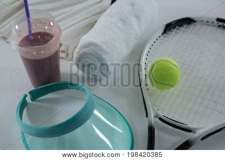 High angle view of racket with sun visor by drink and napkin on white background