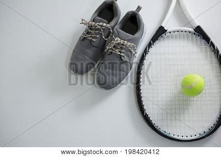Close up of racket with tennis ball by sports shoe on white background