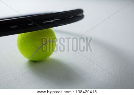 Cropped image of tennis racket with ball on white background