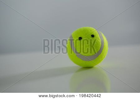 Close up of tennis ball with anthropomorphic face against white background