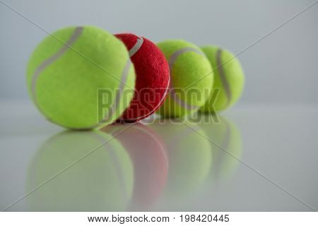 Red and fluorescent tennis ball arranged in row against white background