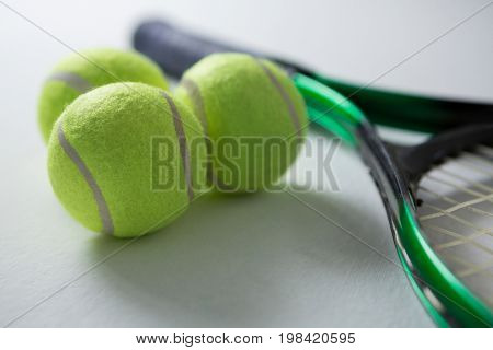 Close up of tennis balls with racket on white background