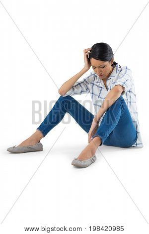 Sad woman relaxing against white background
