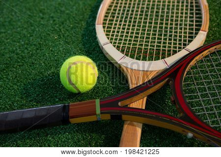 Close up of wooden racket with tennis ball on field