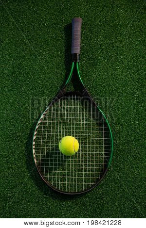 Overhead view of racket with tennis ball on playing field