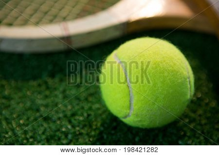 Close up of tennis ball with racket on field