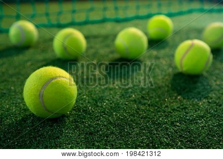 Close up of tennis balls on court by net