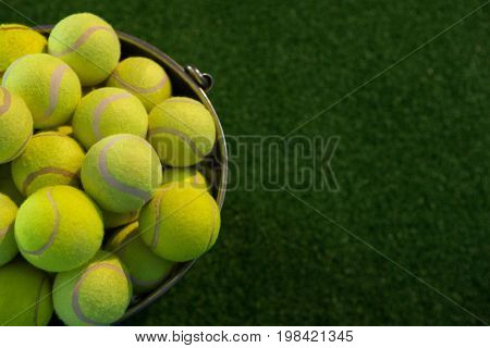 High angle view of fluorescent tennis balls in bucket on field