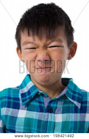 Close-up of cute boy making faces against white background