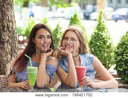 Two positive young women enjoying fresh smoothie in cafe