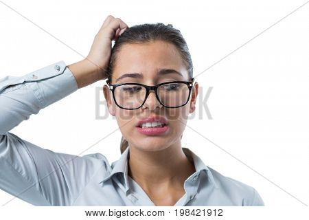 Confused female executive standing against white background